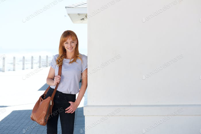 happy young woman standing outside leaning on wall