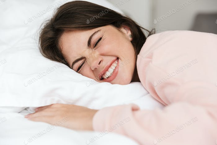 Cheerful lovely young girl wearing pajamas laying in bed