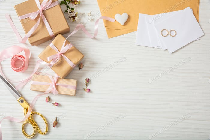 Flat lay and top view of presents and wedding invitations on a white wooden tabletop, copy space.