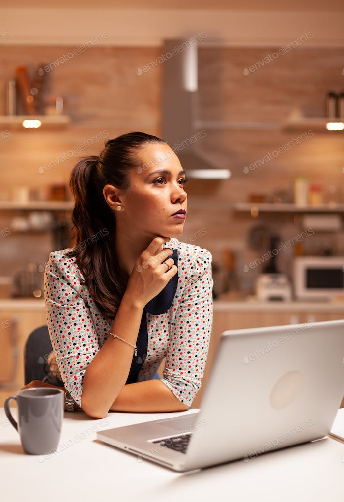 Concentrated businesswoman in home kitchen