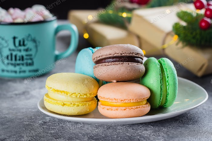 Bright macaroons and mug with hot chocolate with marshmallow. Colorful almond cookies