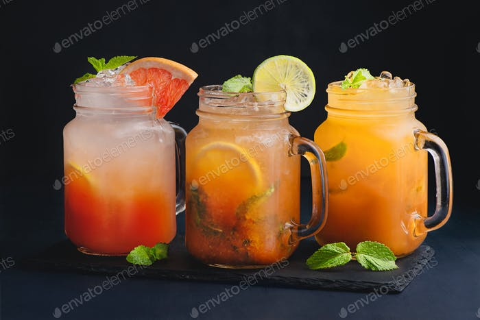 A variety of citrus cocktails vintage glass mason jars with mint and grapefruit. Dark background