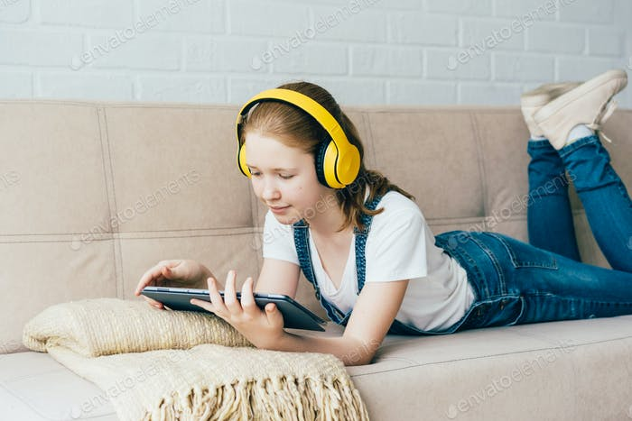 A teenage schoolgirl lying on the couch plays a digital tablet and listens with headphones.