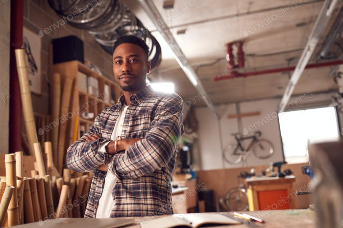 Portrait Of Male Craftsman In Carpentry Workshop For Bamboo Bicycles  Doing Accounts On Laptop