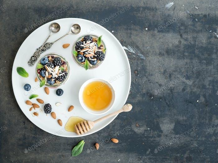 Yogurt oat granola with berries, honey and nuts in glass jars, dark grunge background