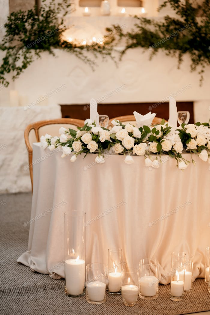 presidium of the newlyweds in the banquet hall of the restaurant is decorated with candles