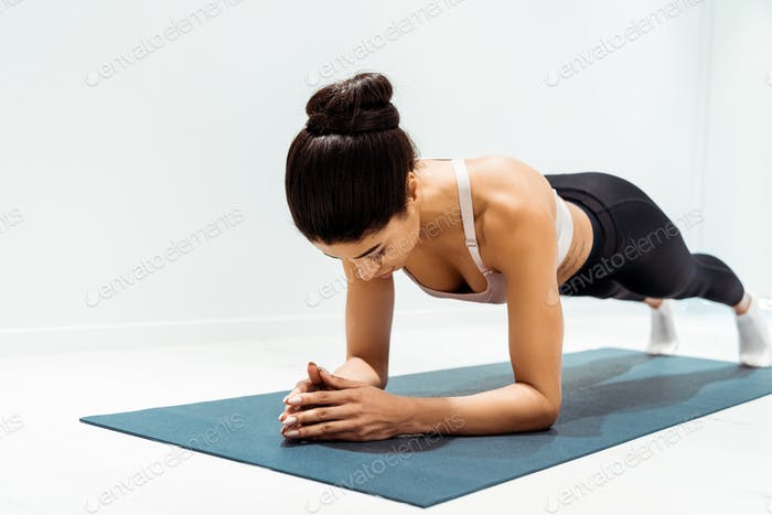 Young wonderful sportive girl doing plank exercise in sports centre