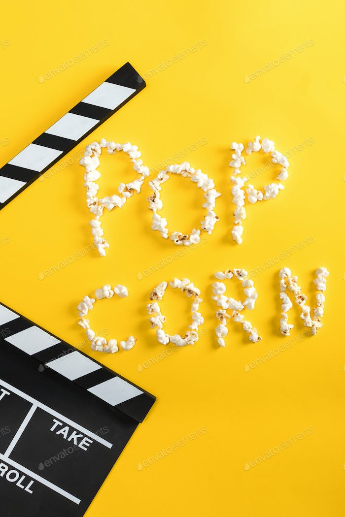 Pop corn lettering made from popcorn and movie clapper on yellow, Movie time concept
