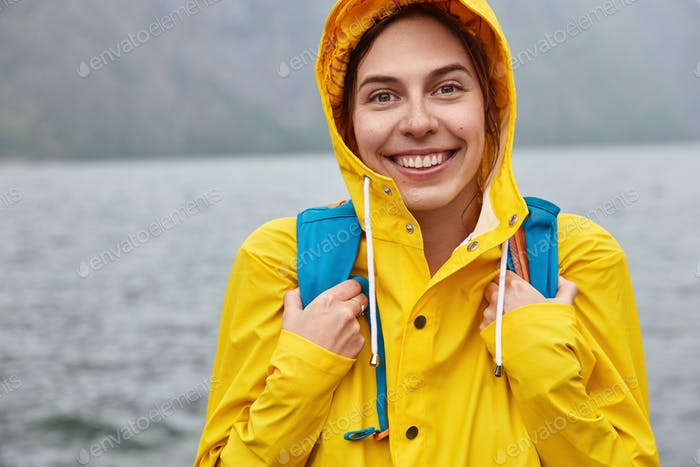 Cropped image of optimistic European woman wears yellow hood, carries backpack, has broad smile, pos