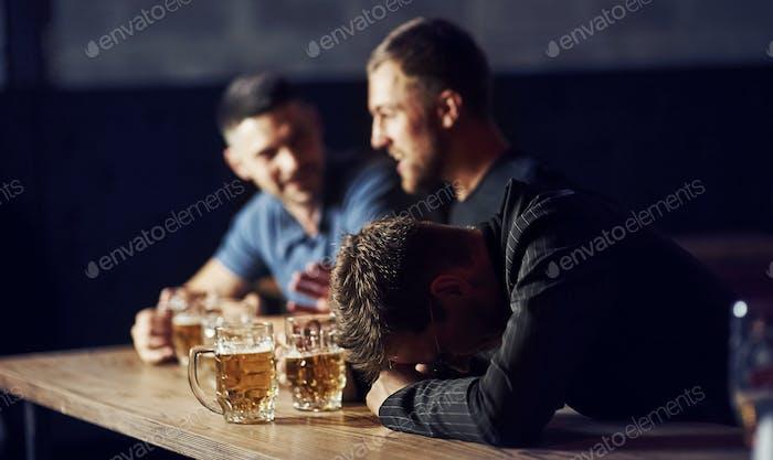 Drei männliche Freunde in der Bar. Unterstützung trauriger Freund. Einheit der Menschen. Mit Bier auf dem Tisch