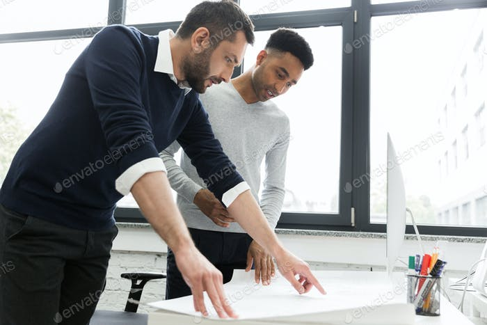 Two young male office workers pointing on a chart