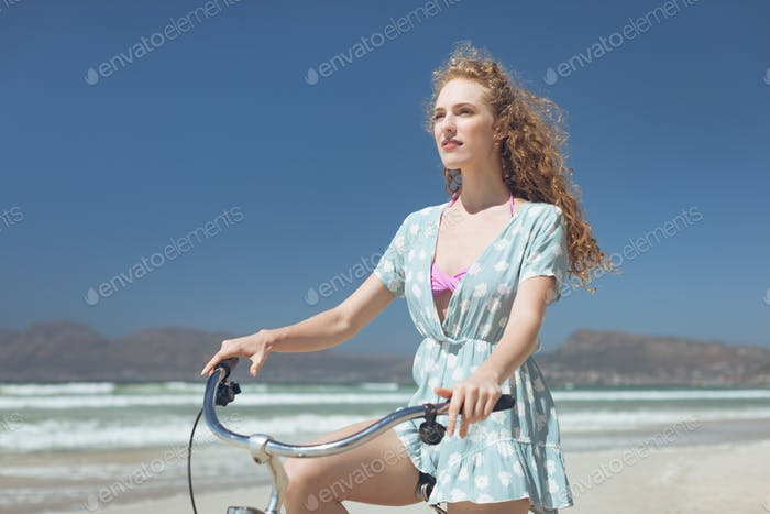 Front view of young Caucasian woman riding bicycle at beach on a sunny day. She is thinking
