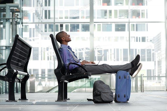 smiling young businessman sitting with laptop and luggage