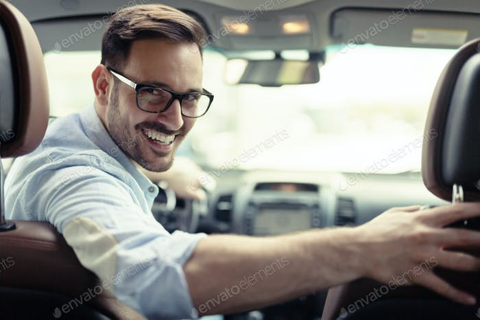 Handsome businessman driving a car to work