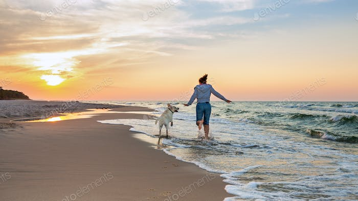 Running Woman with a Dog on the Beach