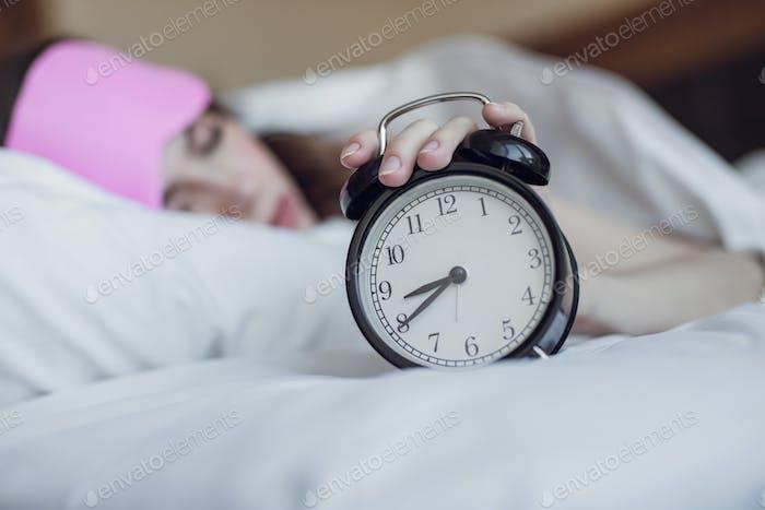 Sleeping girl with an alarm clock