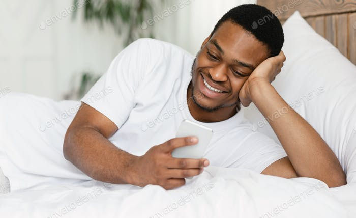 Cheerful Black Guy Using Smartphone Lying In Bed At Home