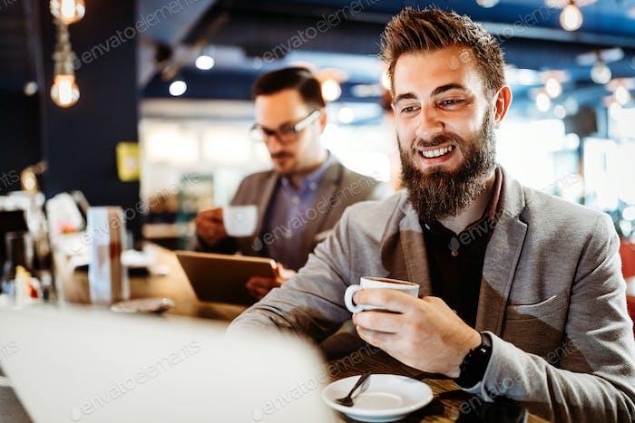 Hombres de negocios alegres que usan computadora portátil en la reunión