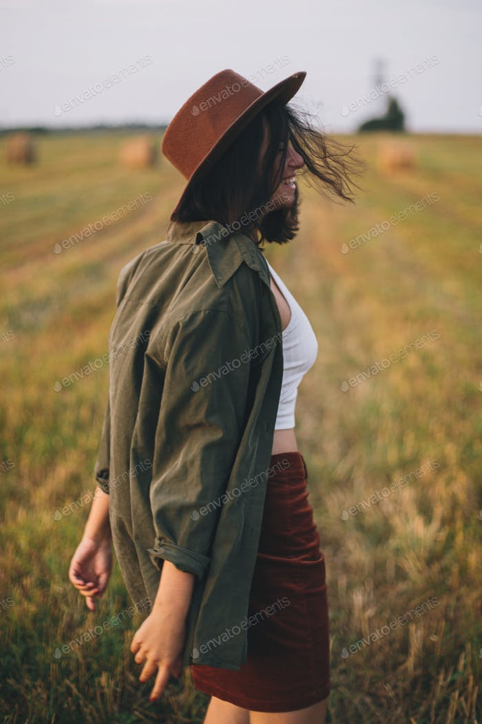 Schöne unbeschwerte Frau mit Hut, die im Abendsommerfeld spaziert und lächelt. Entspannen auf dem Land