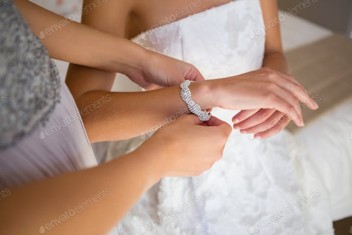 Midsection of bridesmaid dressing bride in fitting room