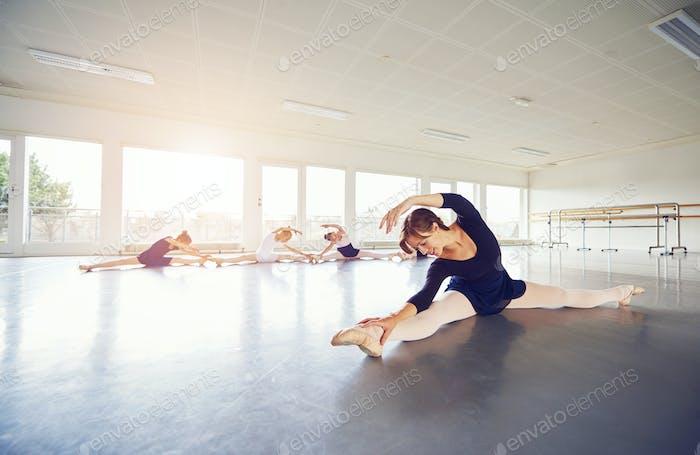 Woman and ballerinas group making leg split on floor