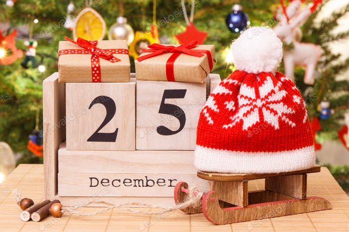 Date 25 December on calendar, gifts with sled and cap, christmas tree