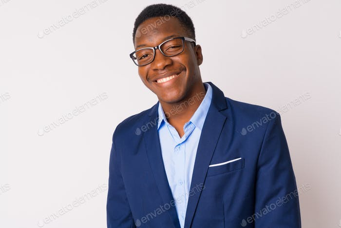 Face of young happy African businessman with eyeglasses smiling