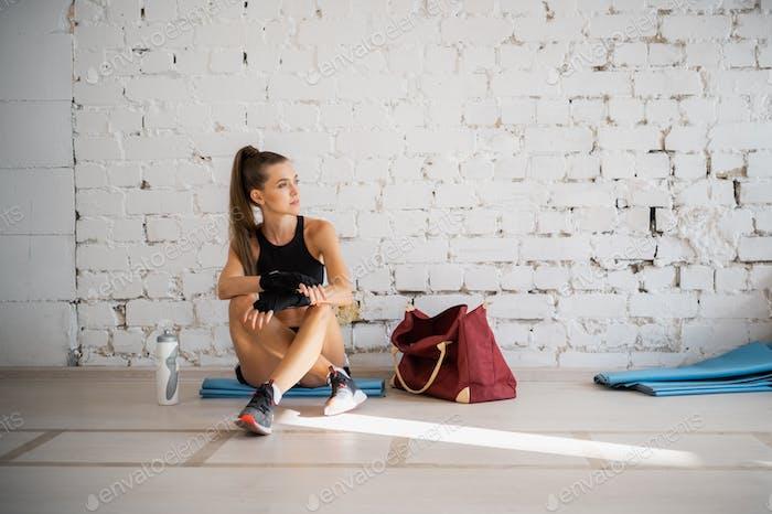 Девушка отдыхает после индивидуальной тренировки с профессиональным боксером в ярком