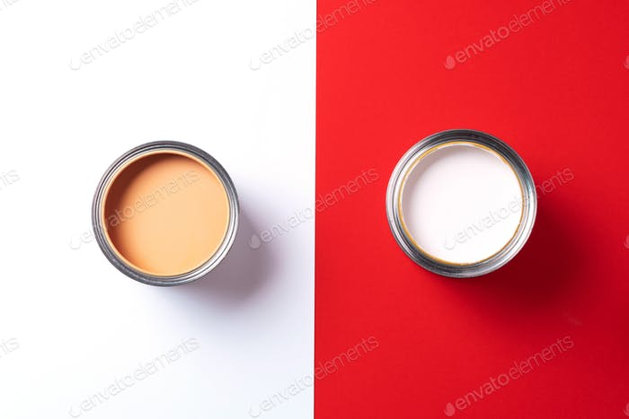 Open paint cans on trendy red and white background. Top view, copy space. Appartment renovation