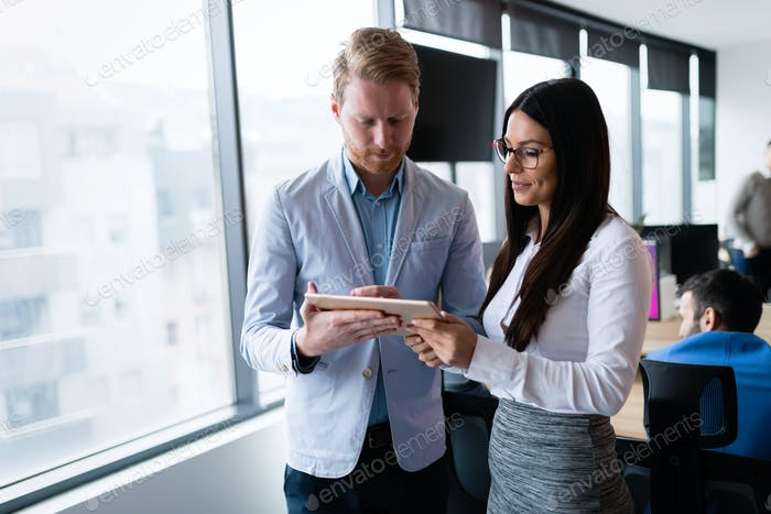 Attractive business couple using tablet in their company