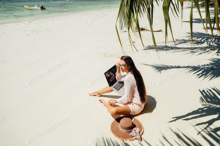 Remote working woman on beach in tropics