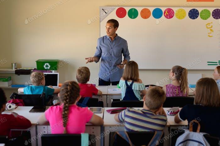 Male school teacher standing in an elementary school classroom with a group of school children