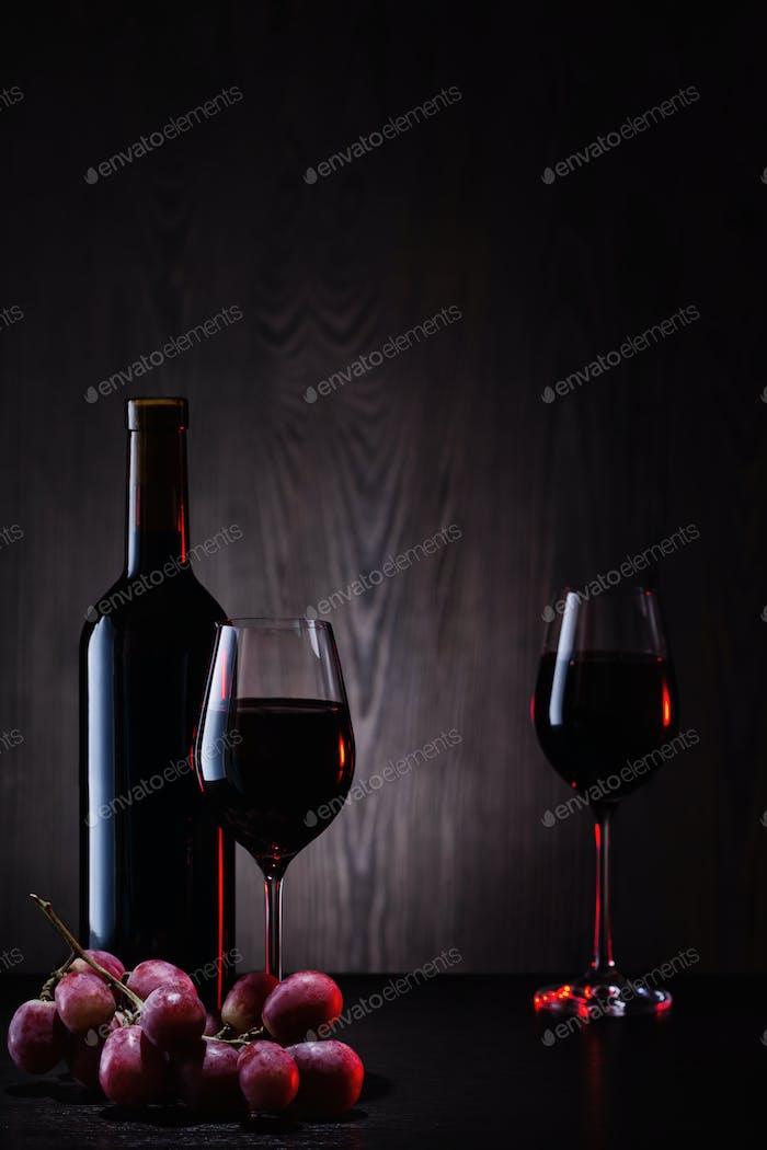 Rotwein in Gläsern und Flasche mit Trauben