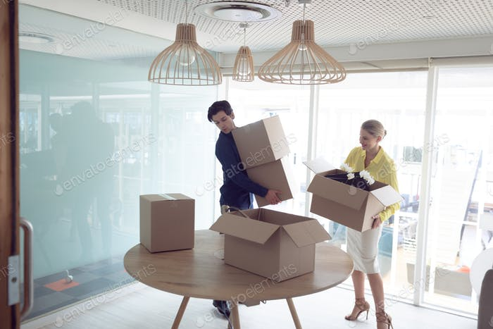 Front view of Caucasian male and female office executives holding cardboard boxes in office
