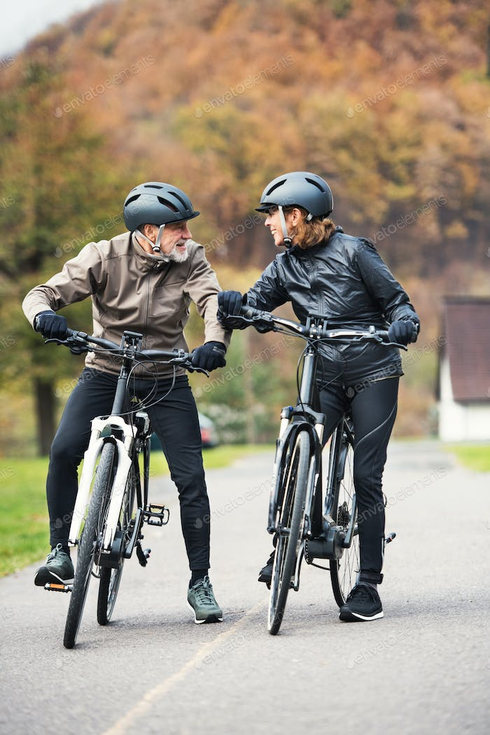 Active senior couple with electrobikes standing outdoors on a road in nature.