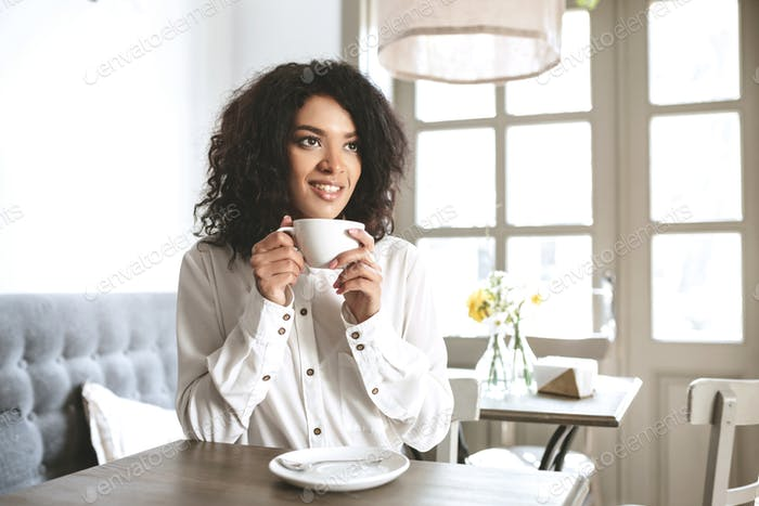 Young African American girl in white shirt sitting in restaurant with cup of coffee in hands