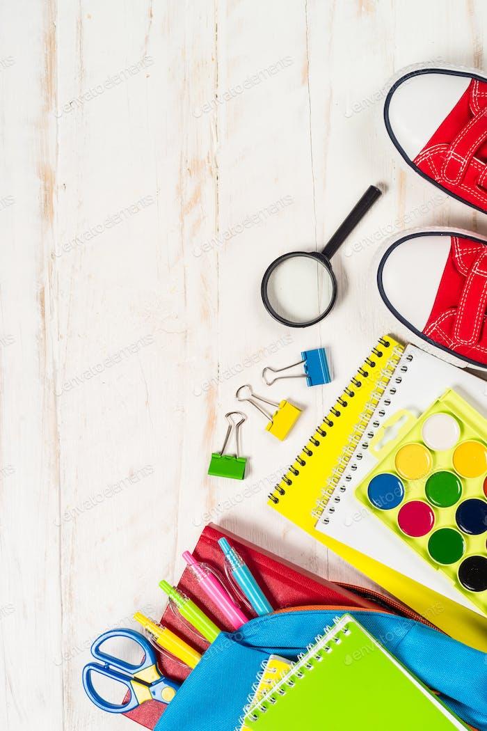 Schulrucksack mit Schreibwaren auf weißem Hintergrund