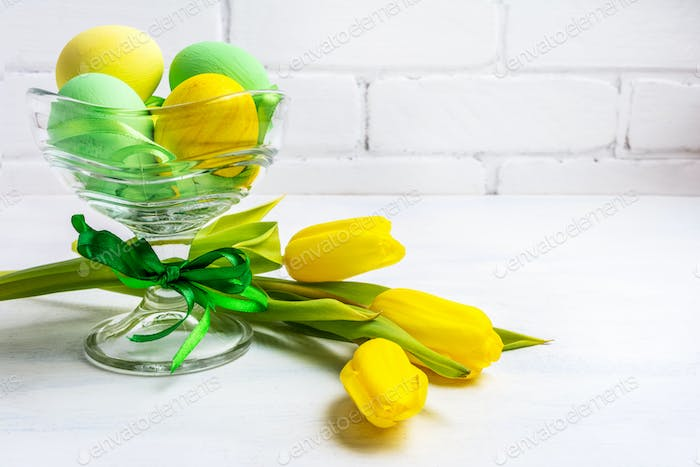 Easter green eggs, yellow tulips, copy space