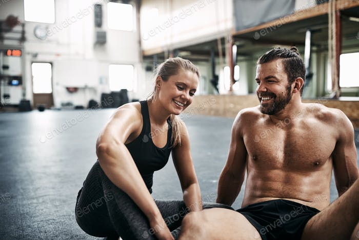 Smiling young couple sitting together on a gym floor