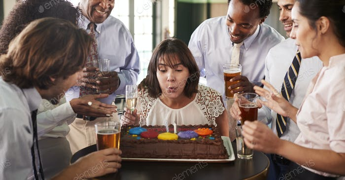 Businesswoman Blowing Out Candles On Birthday Cake At Celebration In Bar With Colleagues