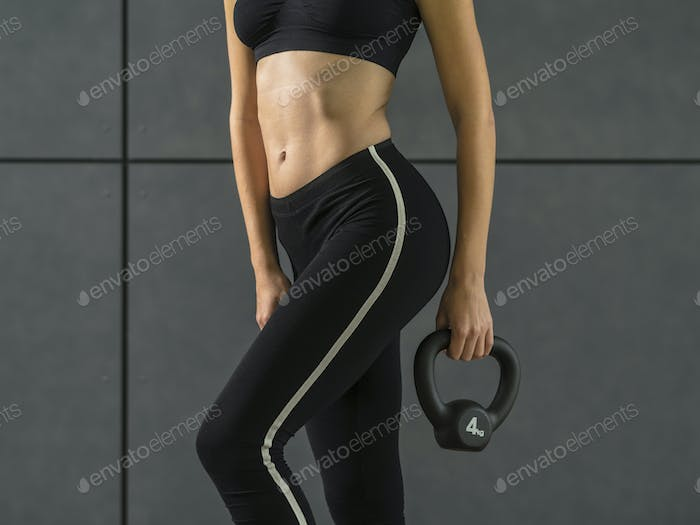 Fit young woman exercising with a kettlebell