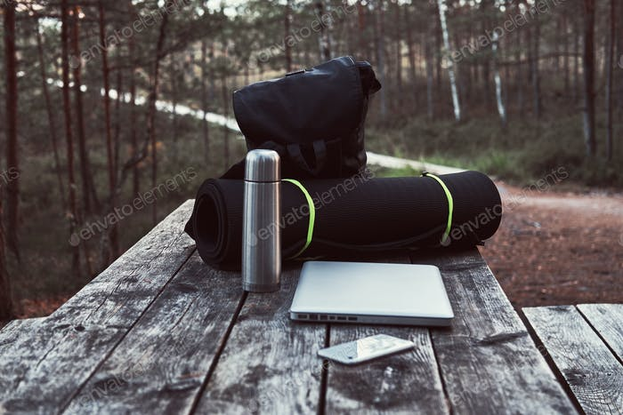 Backpack, tourist mat, laptop, smartphone and thermos bottle on a wooden table