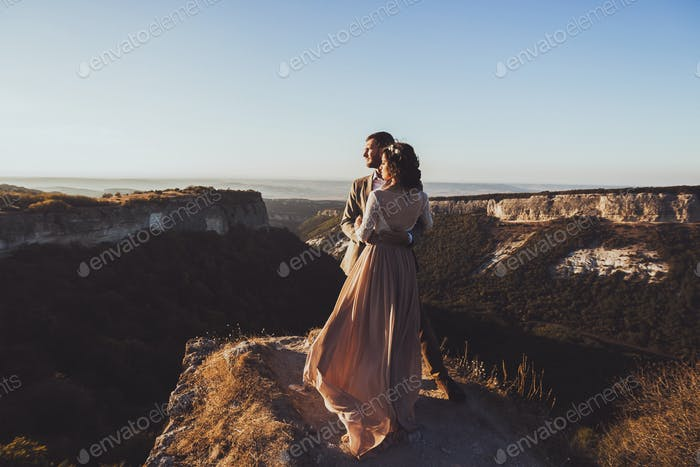Bride and groom walking in mountains at sunset. Around the stunning scenery with views of mountains