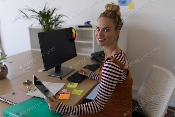 Female executive while using digital tablet and working on computer at desk in office