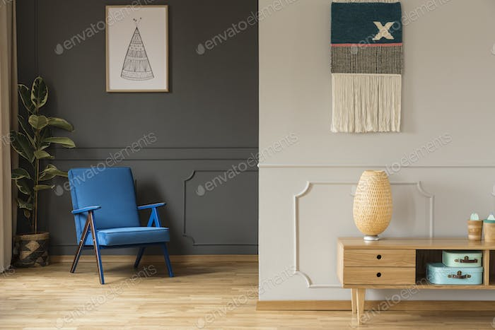 Blue armchair against grey wall with poster and wooden cabinet i