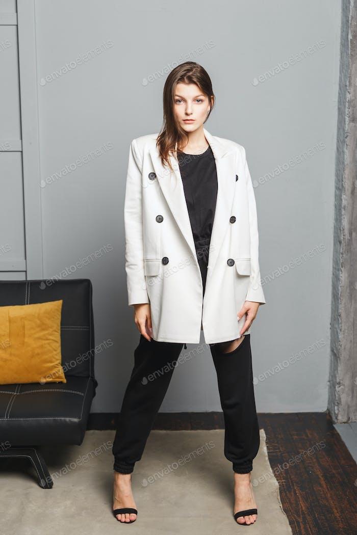 Молодая элегантная женщина в белом негабаритных блейзер и черные рваные брюки. Интерьер портрет