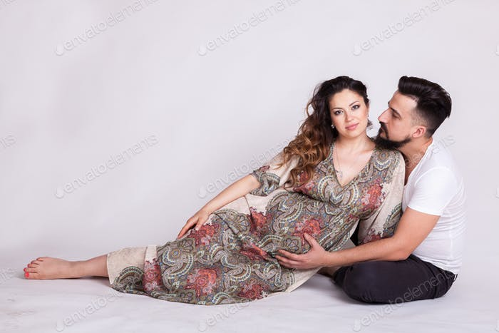 Pregnant wife with her husband in studio photo