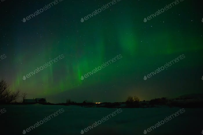 village with houses under sky with beautiful northern lights in iceland