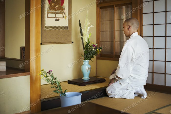Side view of Buddhist monk wearing white robe kneeling in front of vase with flowers.