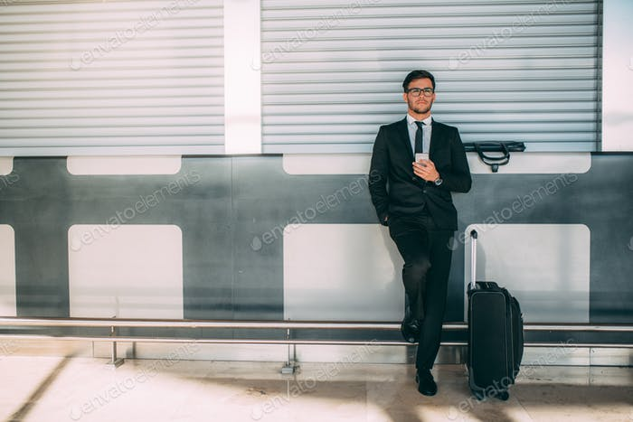Young business man standing on the phone with the suitcase at the airport waiting for the flight